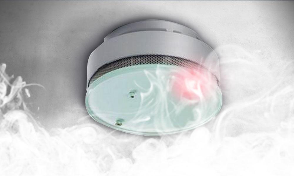 Foto eines aktiven Rauchmelders an der Zimmerdecke. Rauch im unteren Bereich