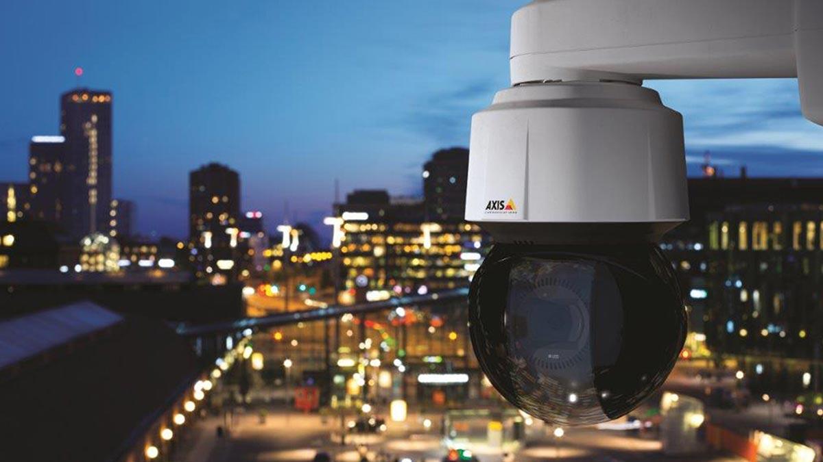 Axis Videokamera hängt an Aussenwand und bewacht ein Geschäftsgebäude. Es ist Nacht.